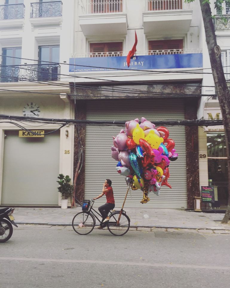 Woman carrying balloons on her bike in Hanoi.